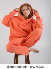 girl teenager with blond hair in a warm tracksuit on a light background
