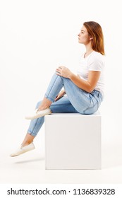 Girl teenager in blue jeans sits on cube in white studio, full body, profile