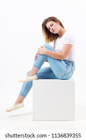 Girl teenager in blue jeans sits on cube in white studio, full body