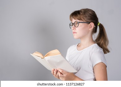 Girl teenager with book and wearing glasses on a gray background