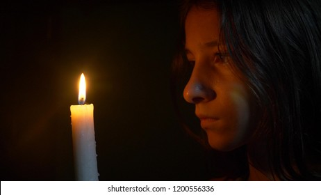girl teenager with a burning candle. close-up, the face of a girl looking at a candle flame.