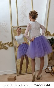 girl teenager in dress dressing up at mirror