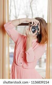 Girl teenager in dress stands with retro camera between curtains near window in studio