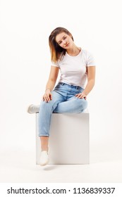 Girl teenager in jeans sits in cube on white studio, full body