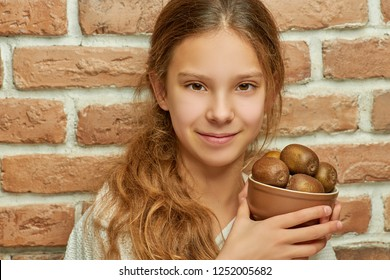 Girl teenager with long hair holding plate with kiwi on background of brick wall.