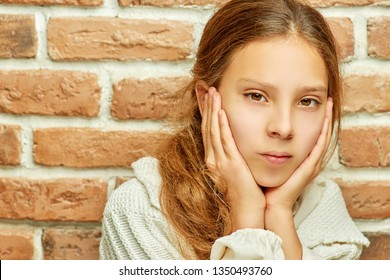 Girl teenager with long hair looks thoughtfully against brick wall.