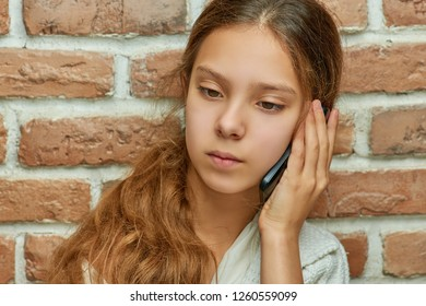 Girl teenager with long hair talking on cell phone against brick wall.
