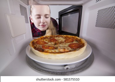 Girl teenager open the microwave. Closing his eyes smelling aroma of fresh cooked pizza. In the studio on a white background