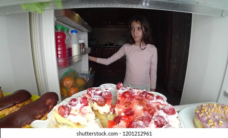 girl teenager opens the refrigerator at night. night hunger. diet gluttony