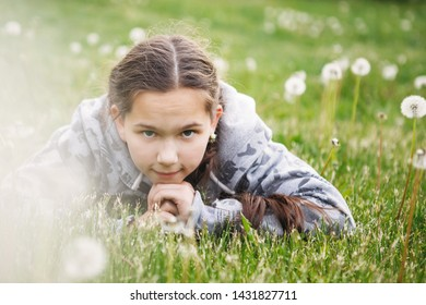 Girl teenager with pigtails lying on the grass. Fluffy blowballs. Happy childhood. Natural life.