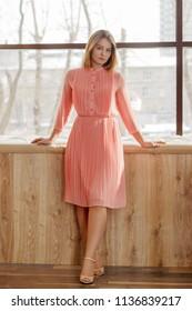 Girl teenager in pink dress stands near soft window sill in studio, full body