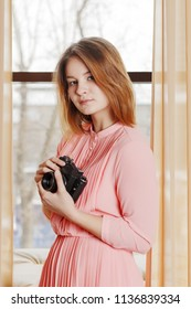 Girl teenager in pink dress stands with retro camera between curtains near window in studio