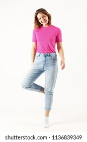 Girl teenager in pink t-shirt and jeans stands in white studio, full body