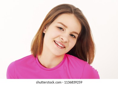 Girl teenager in pink t-shirt poses in white studio, close up