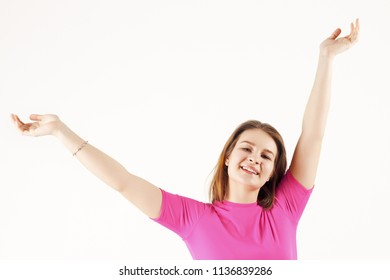 Girl teenager in pink t-shirt poses with raised hands in white studio, close up