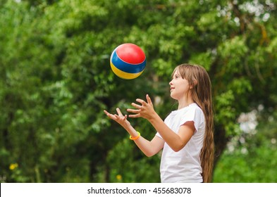 The girl the teenager, plays in park, a ball, throwing it.