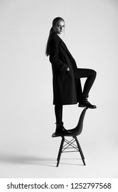 Girl teenager in stylish clothes standing on a chair. Isolated studio.