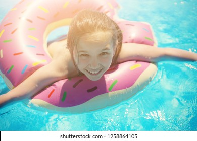 Girl teenager in a swimsuit swims with an inflatable ring in the pool with blue water.