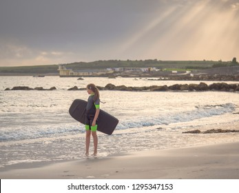 Girl teenager in wet suit, standing and looking at  ocean, holding small surf board. Blackrock beach, Salthill, Galway city Ireland, Famous Black rock jumping tower in the background