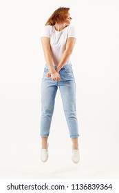 Girl teenager in white t-shirt and jeans jumps in white studio, full body