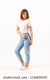 Girl teenager in white t-shirt and jeans poses in white studio, full body