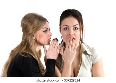 girl telling a secret to her friend's ear. top secret