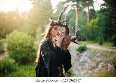 A girl in a terrible mask with horns is standing in nature. A man in a black cloak. The pagan witch conjures. Fantasy image