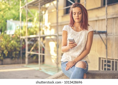 Girl texting and listening to music in the city. Girl enjoys a good time in the sunlight