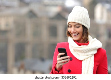 Girl texting in a mobile phone warmly clothed in the street in winter