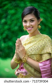 The girl in a Thai national dress. She was smiling, greeting and making hand sawasdee. Sawasdee is Thailand greeting.