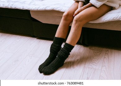a girl with thin legs in black socks sitting on the bed, recently woke up