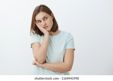Girl thinks party lame. Bored young european female with short brown haircut leaning head on palm gazing at upper right corner thinking using imagination to entertain herself while dying from boredom