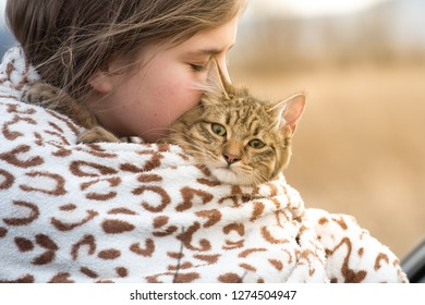 Girl thirteen years with her cat outdoor in winter cold day real friends