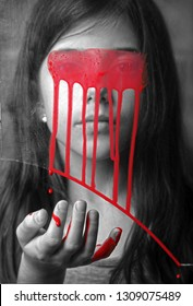 A girl through the glass with dripping red paint