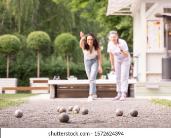 Girl throw boule friends playing petanque in city park background
