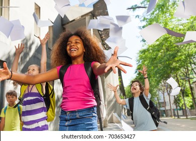 Girl throw papers in the air for friends to catch