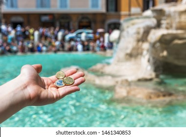 Girl is throwing coin at Trevi Fountain for good luck. A girl hand keeping coin. Trevi Fountain, Rome, Italy.