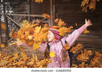 girl throws maple leaves. autumn fun. school holiday. child playing in leaf fall.