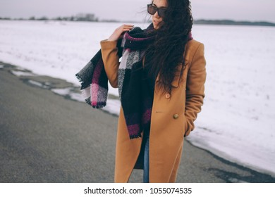The girl throws a scarf around her neck