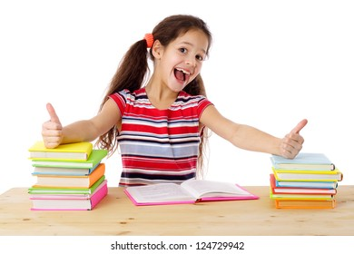 Girl with thumbs up sign sitting on the table with stack of books, isolated on white