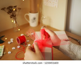 A girl ties a ribbon of tulle on a gift, preparing a surprise, visible hands and decorative articles