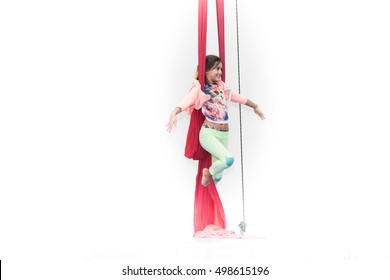 Girl tilts on red silk during circus class