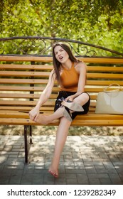The girl, tired of heels, takes off her shoes from her feet and sits barefoot on a park bench