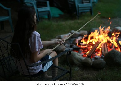 Girl toasting s'more over campfire.