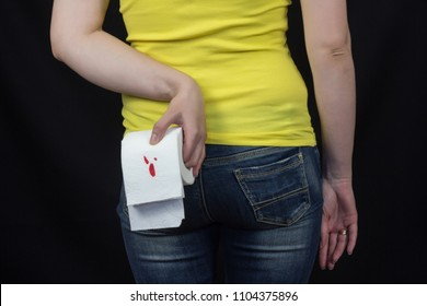 Girl with toilet paper with blood, hemorrhoids, black background
