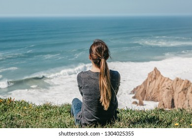 The girl at the top of the cliff in solitude admires the beautiful view of the Atlantic Ocean.