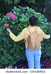 A girl with a topknot in a corduroy jacket and jeans with a knapsack on her back embraces a bouquet of hydrangeas growing in Italy.
