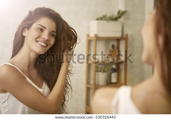 鏡を見ながら髪に触れ、微笑む少女