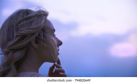 Girl touching her lips, thinking about beloved man, sadly looking into distance