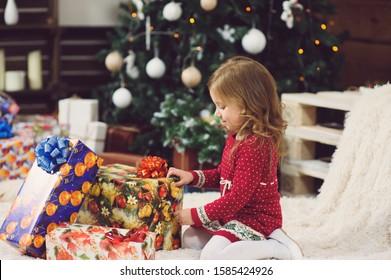 girl touching present box under Chritmas tree